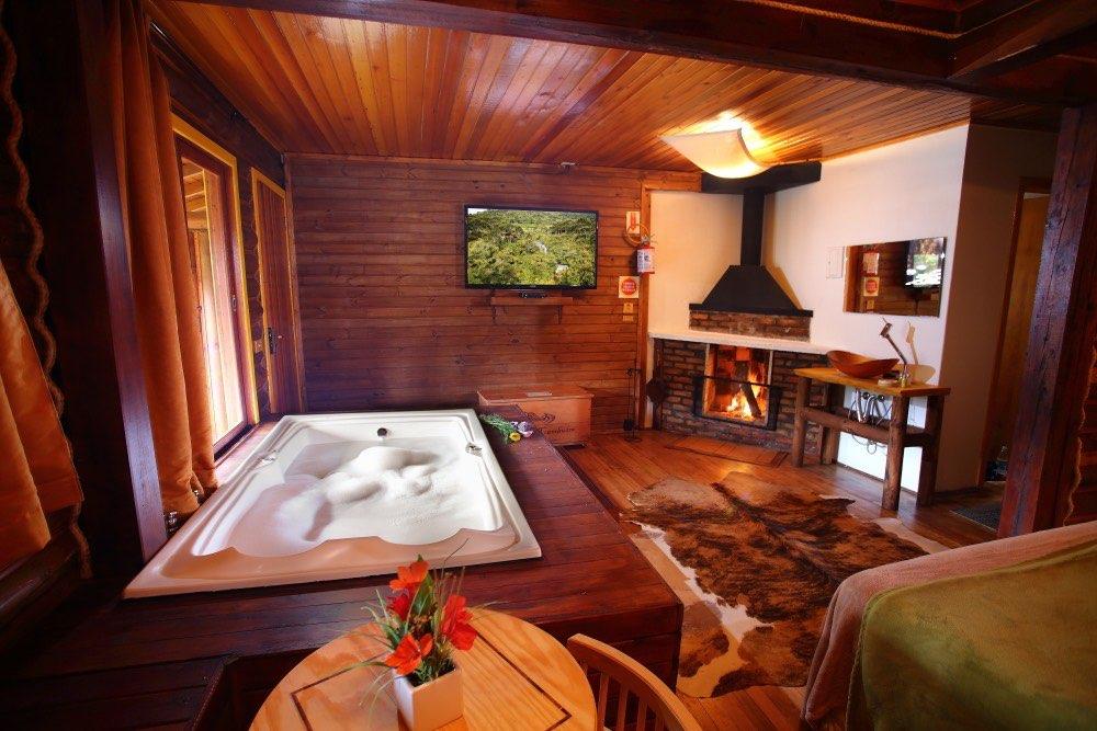 Vista da mesa no interior da cabana. Cuba de pia externa ao WC e televisor grande.